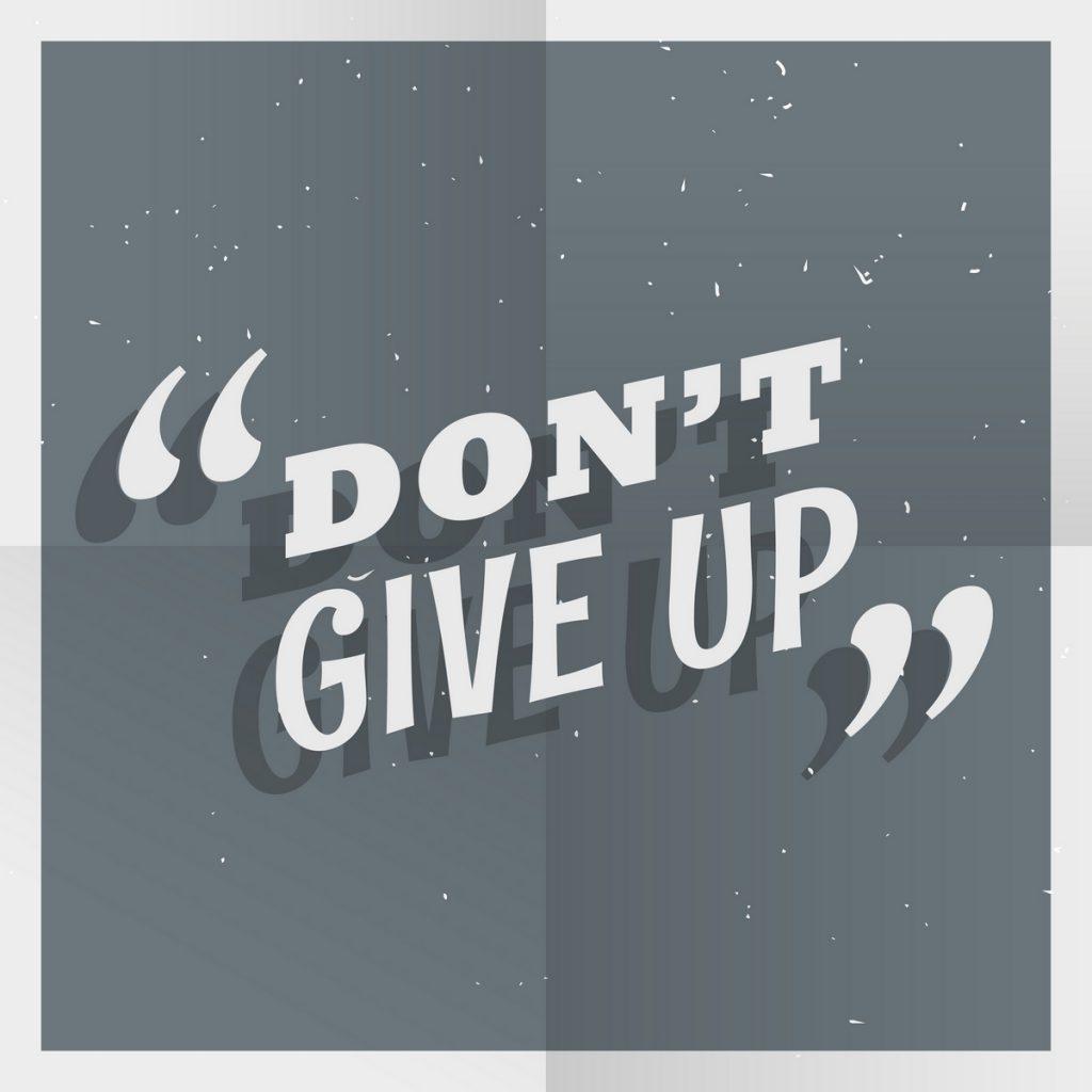 """Papel com marcas de dobrado. Nele, está escrita a frase em inglês """"don't give up""""."""