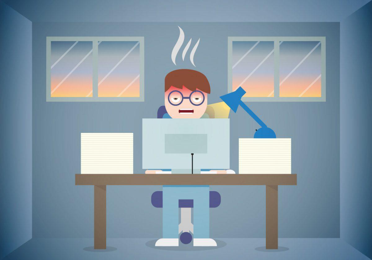 Garoto sentado com cara de desesperado mexendo em um computador que está sobre a mesa representando os erros que atrapalham a aprovação.